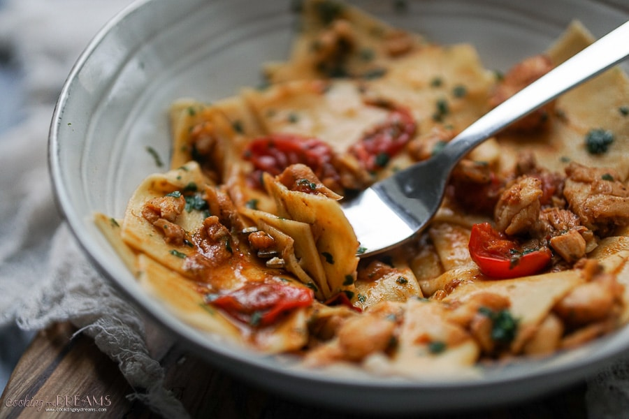 macro shot of fork holding pasta with cod and tomatoes