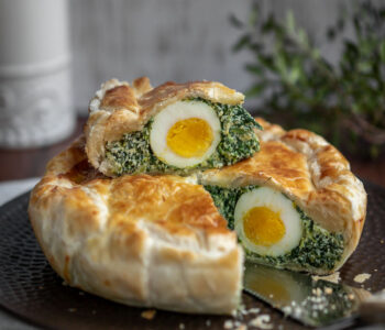 torta pasqualina spinach and ricotta quiche with a slice on top