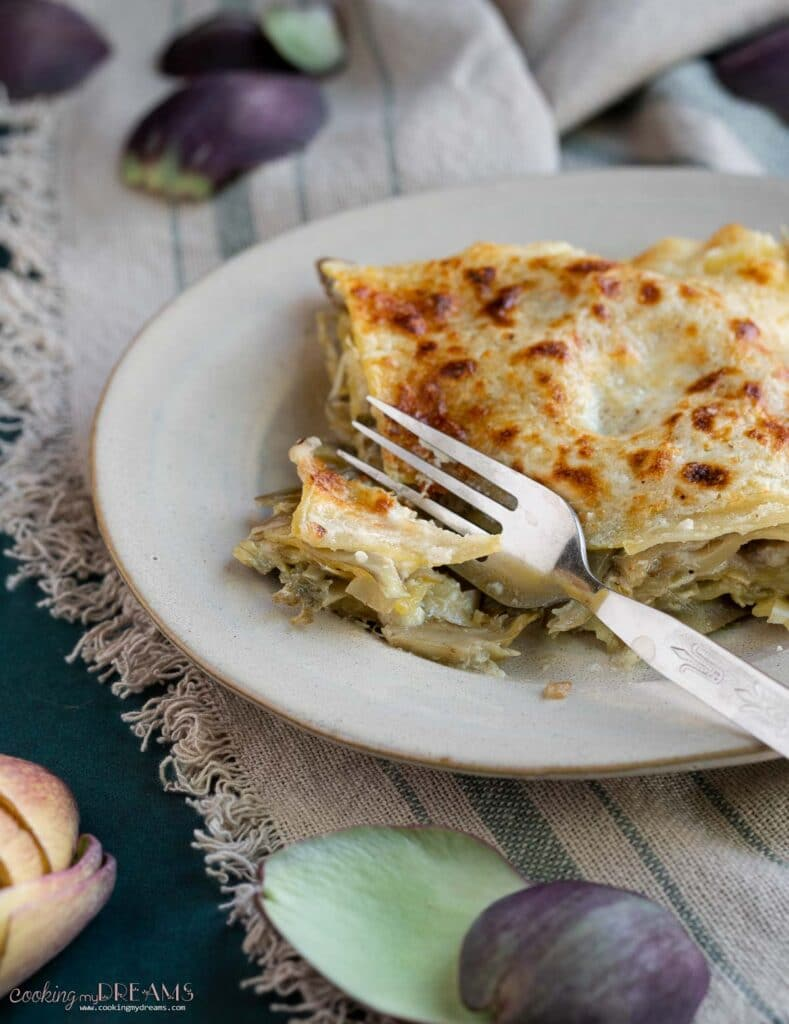fork cutting into a portion of artichoke lasagna on a plate