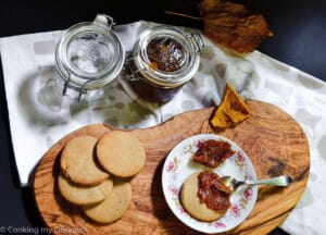 teaspoon spreading pumpkin jam on a chestnut cookie next to more cookies