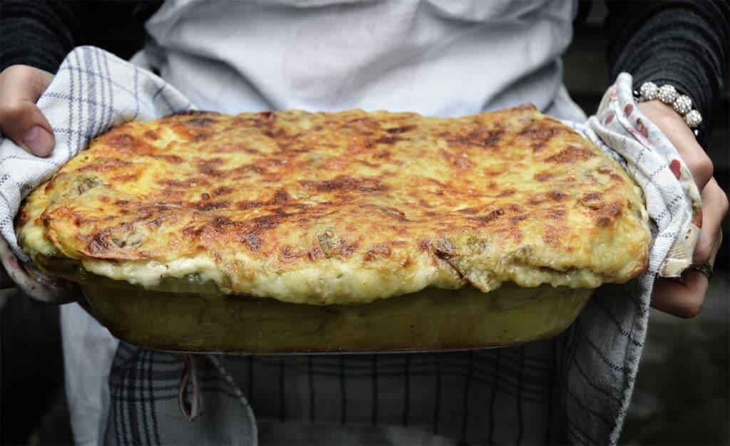 woman holding a lasagna tray