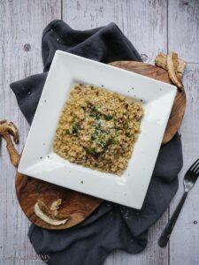 white square plate with mushroom bulgur risotto