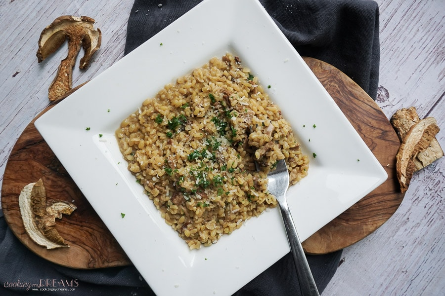 white square plate with mushroom bulgur and a fork