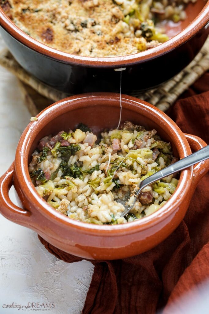 small terracotta dish with rice, cabbage and bacon with a spoon