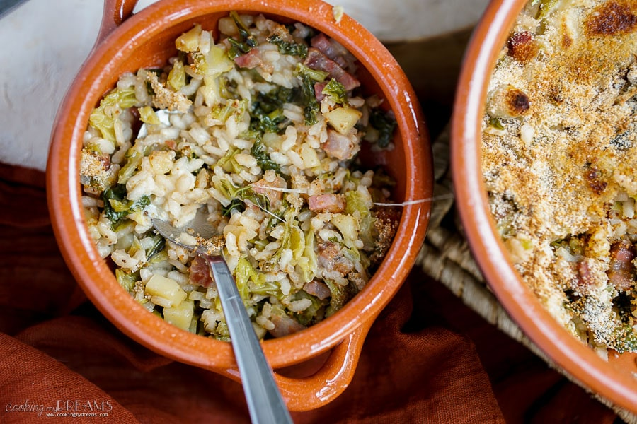 overhead dish with rice savoy cabbage and bacon with a spoon