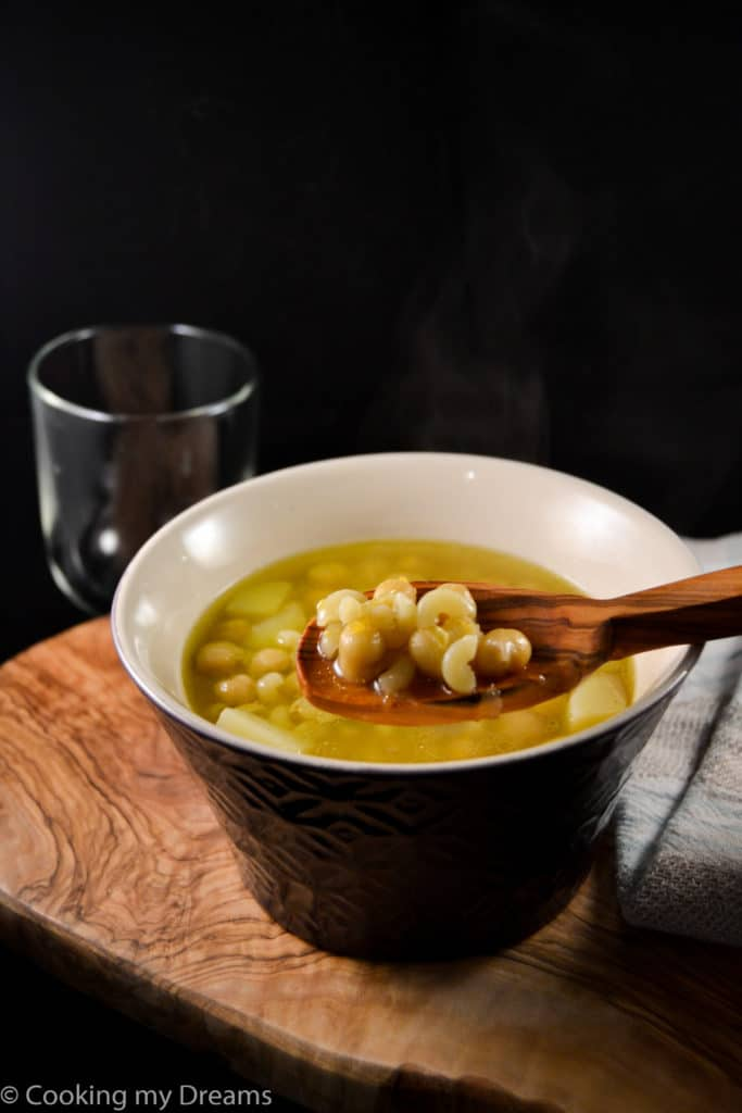 wooden spoon holding chickpea soup