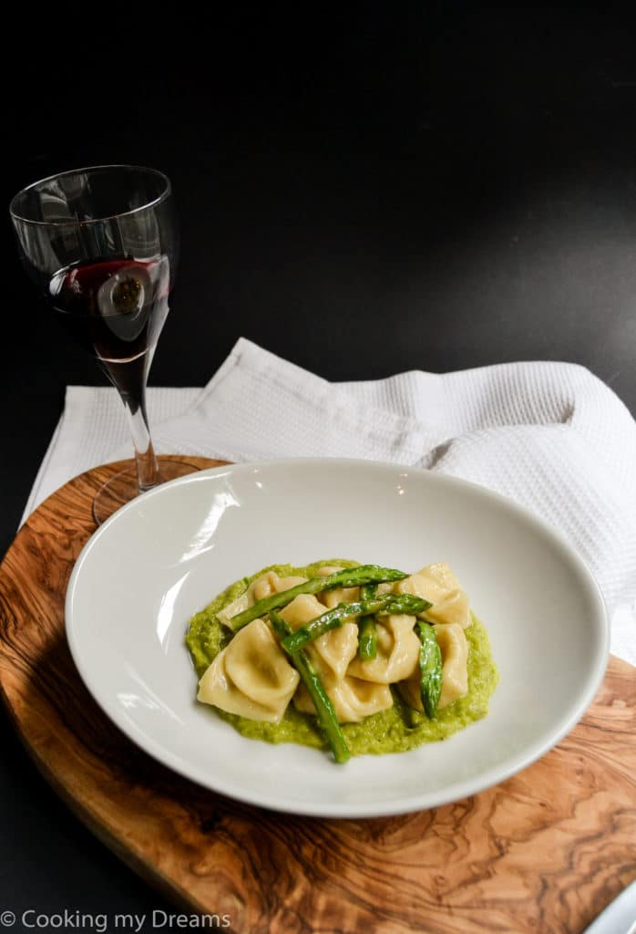white plate with tortelli and asparagus with a glass of red wine