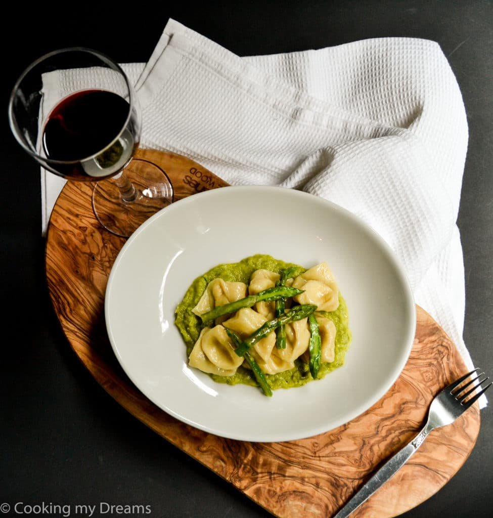 overhead dish with tortelli and asparagus with a glass of red wine