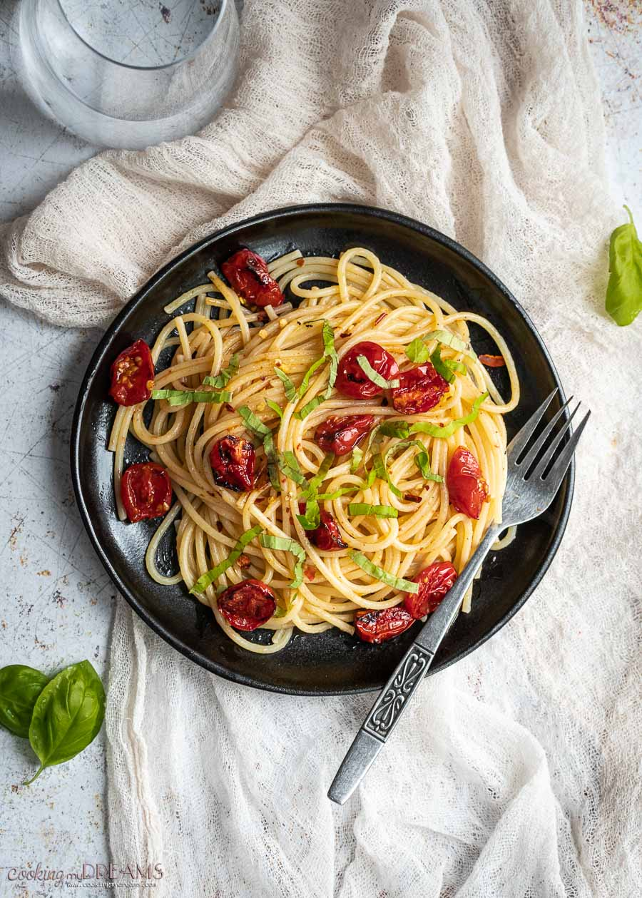 black plate with spaghetti and roasted cherry tomatoes
