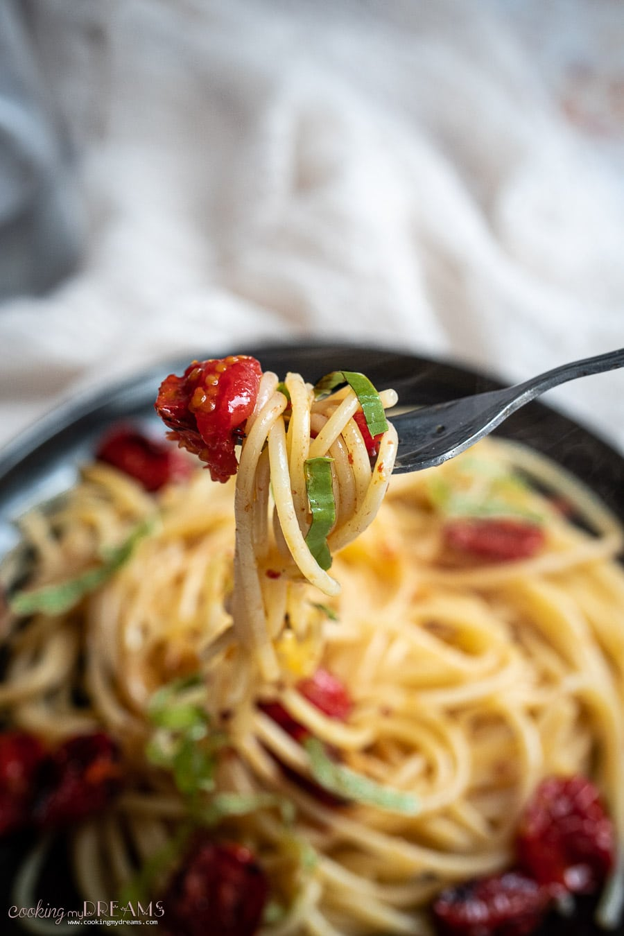 fork holding spaghetti with chili garlic oil and tomatoes