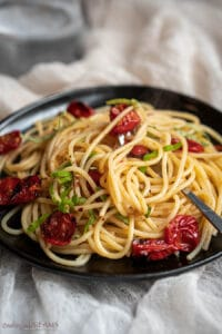 black plate with spaghetti with garlic chili oil and roasted cherry tomatoes