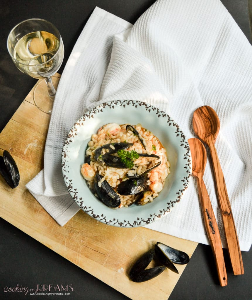 overhead blue plate with seafood risotto, mussels and 2 wooden spoons