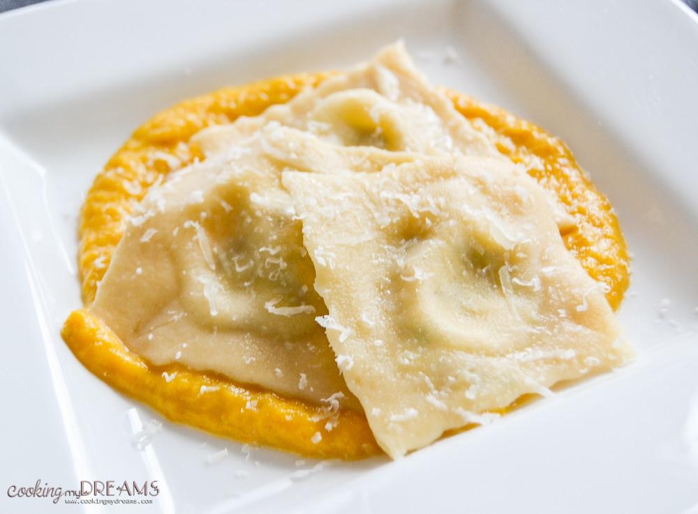 Ravioli on creamy pumpkin sauce on a while plate