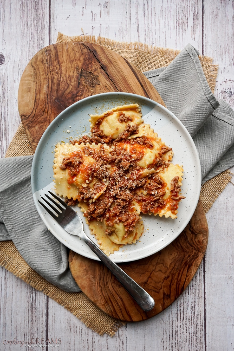 overhead shot of a plate with ravioli and ragù sauce