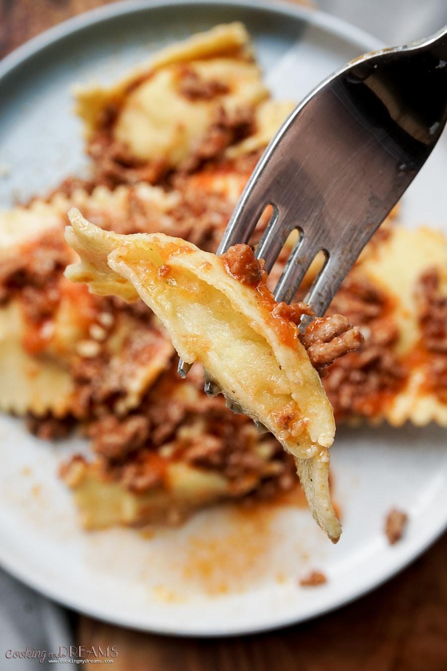 macro shot of half ravioli on a fork showing the potato filling