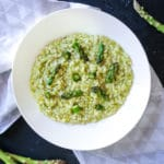 overhead photo of asparagus risotto in white dish