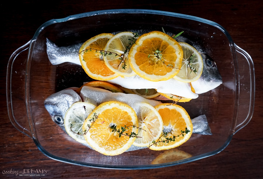 Overhead photo of two raw sea breams with citrus slices on top