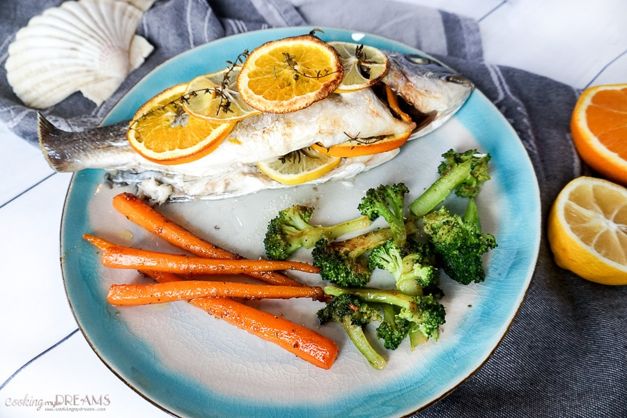 Overhead photo of cooked fish with citrus slices and a side of vegetables