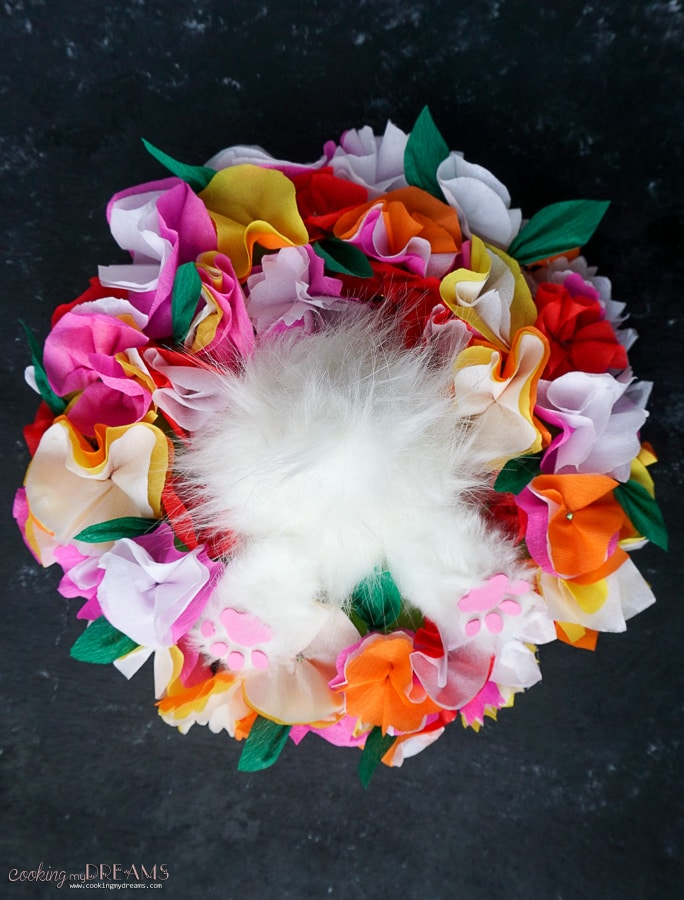overhead shot of easter centerpiece with paper flowers and fluffy bunny on black background