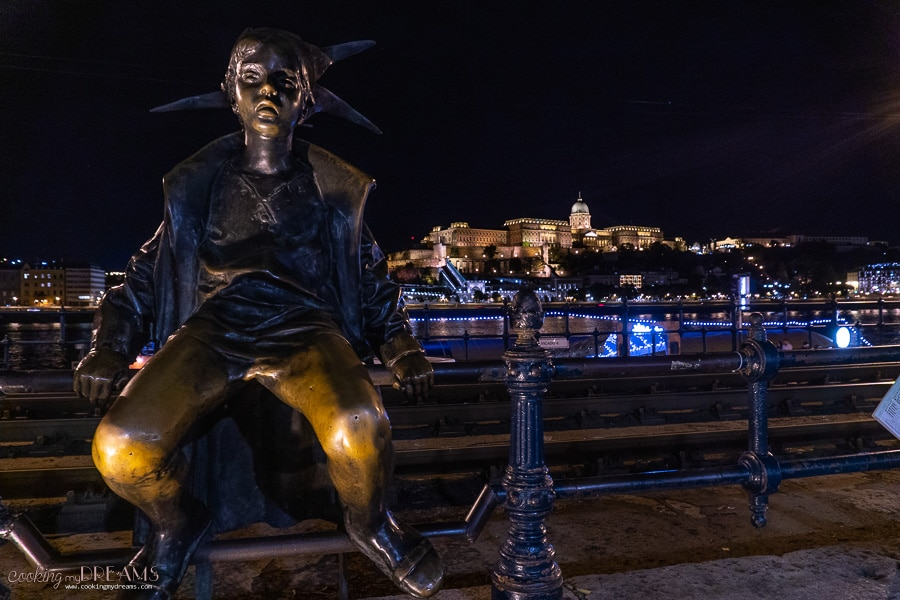 statue overlooking Buda castle at night