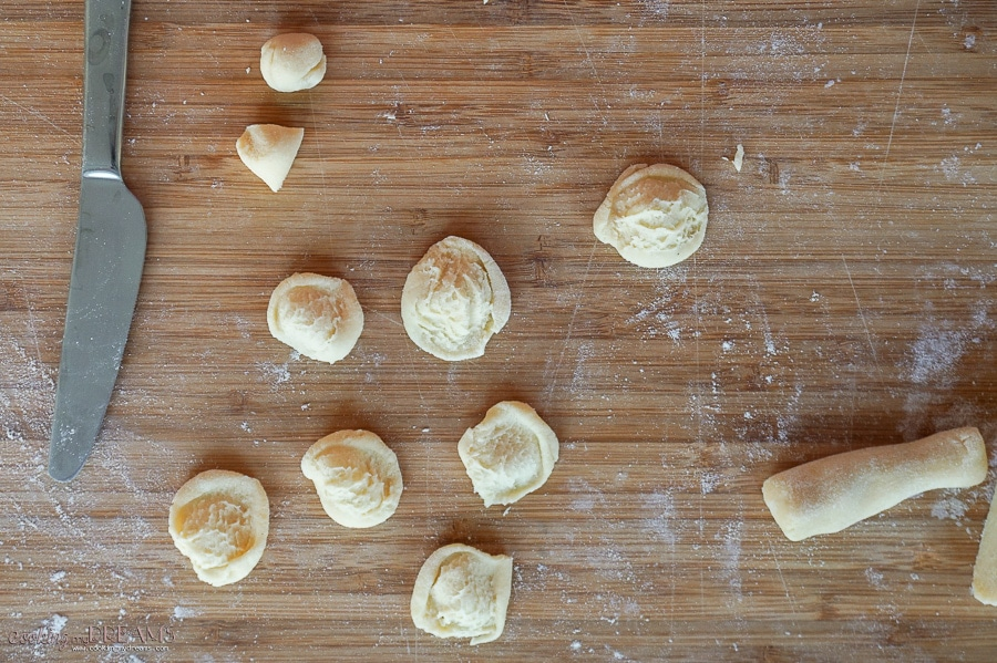 making orecchiette pasta on a board with a knife