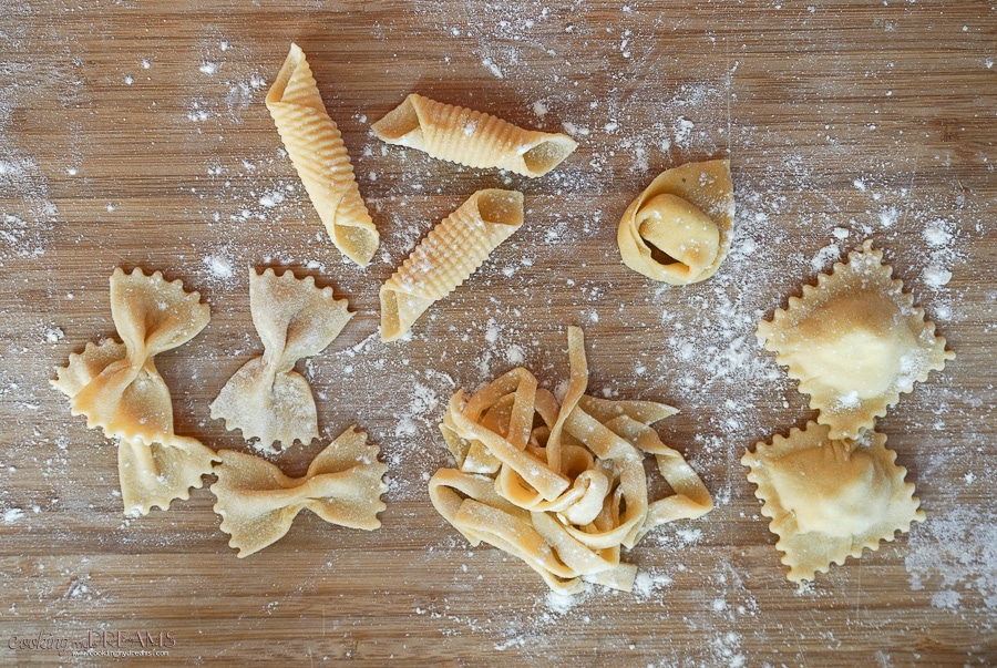 5 different raw pasta shapes on a cutting board dusted in flour