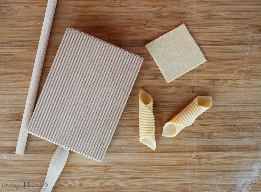 2 raw garganelli pasta next to a gnocchi board