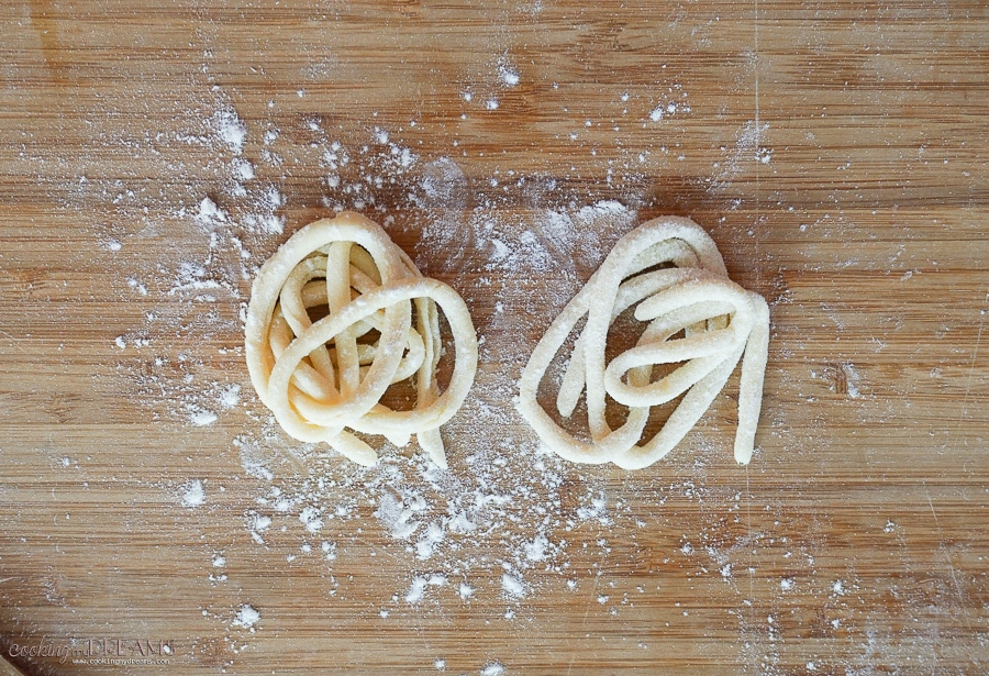 2 pici pasta nests on a cutting board dusted with flour