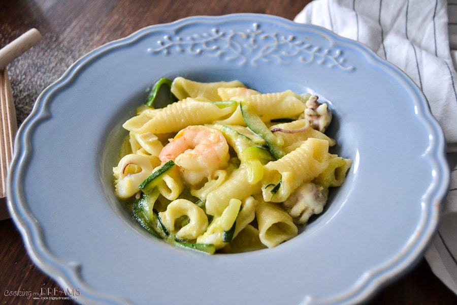 garganelli pasta with seafood and zucchini in a blue plate