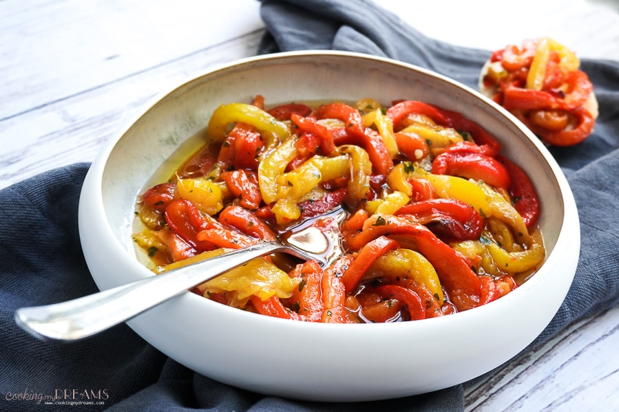 marinated roasted bell peppers in a white bowl with fork