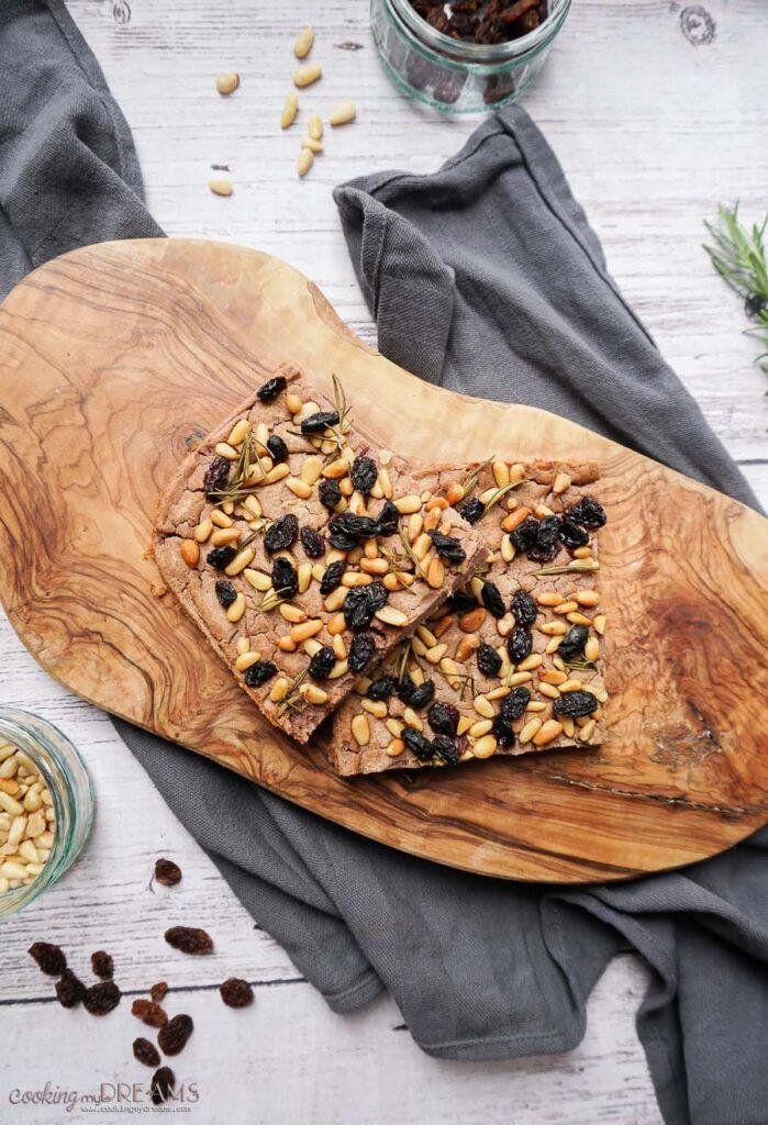 two slices of castagnaccio cake on a wooden board