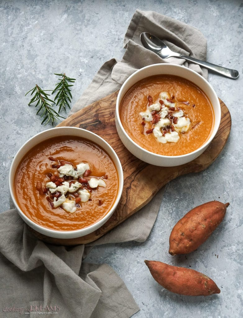 two bowls with creamy sweet potato soup topped with bacon and gorgonzola