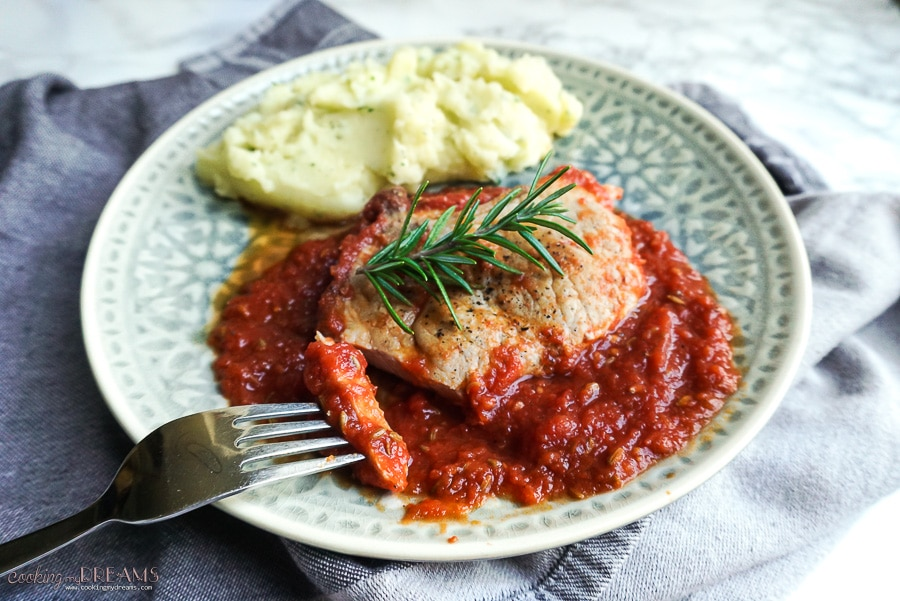 plate with pork chop in tomato sauce and mashed potatoes