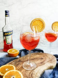 2 glasses of spritz with orange slices and a bottle of aperol