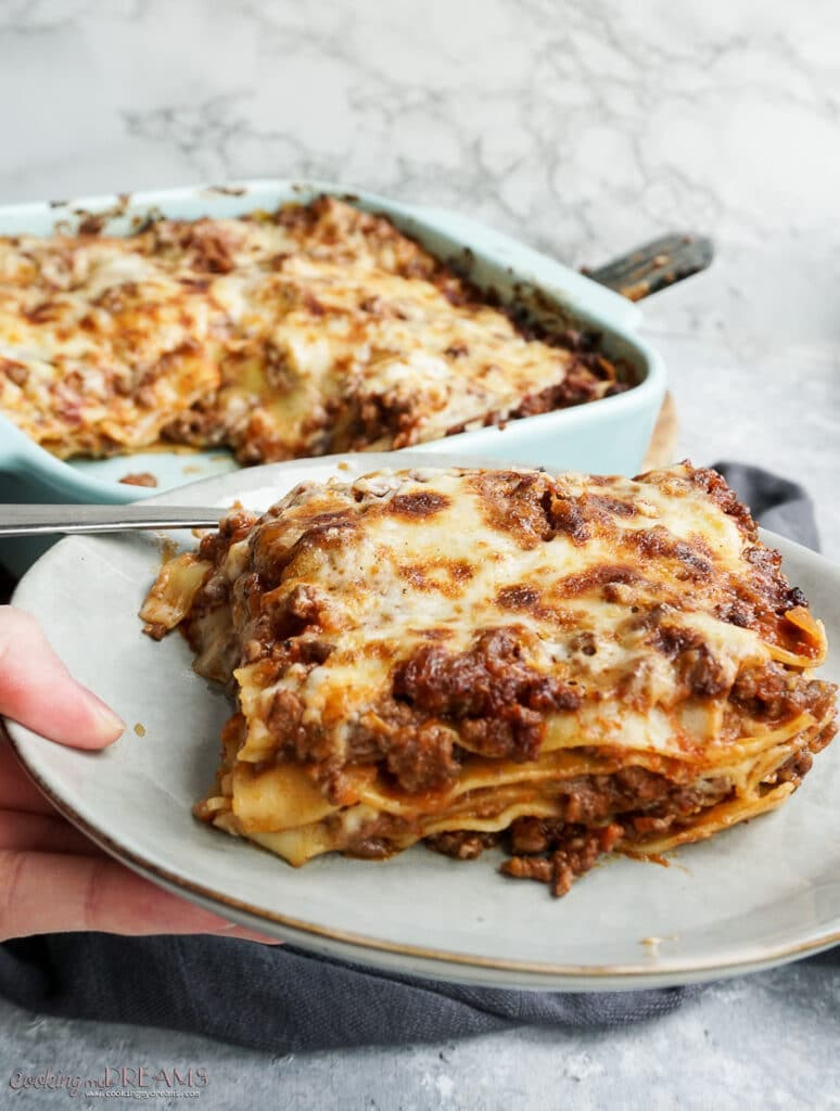 hand holding a plate with a portion of ragù lasagna