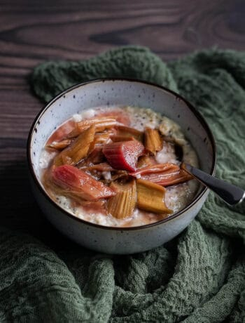 vanilla oatmeal in a bowl topped with roasted rhubarb and a spoon