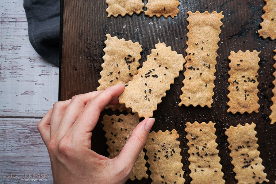hand picking up a cracker from the baking tray