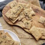 cumin spelt crackers on a plate and on a wooden board