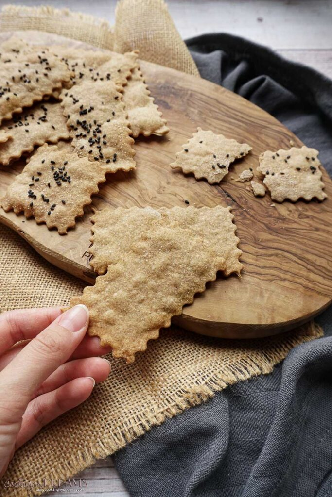 hand picking up a saltine cracker from the wooden board