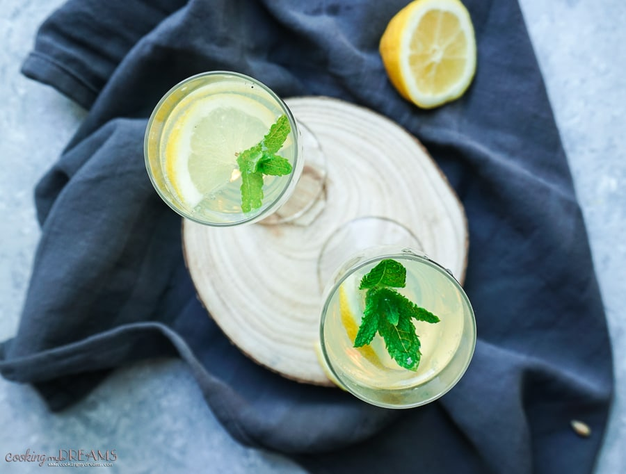 overhead shot of two glasses on a wooden board with mint and lemon