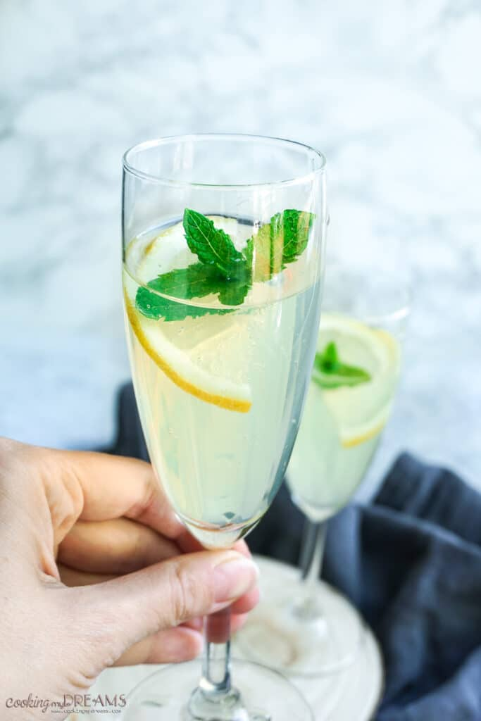 hand holding a glass with limoncello prosecco drink