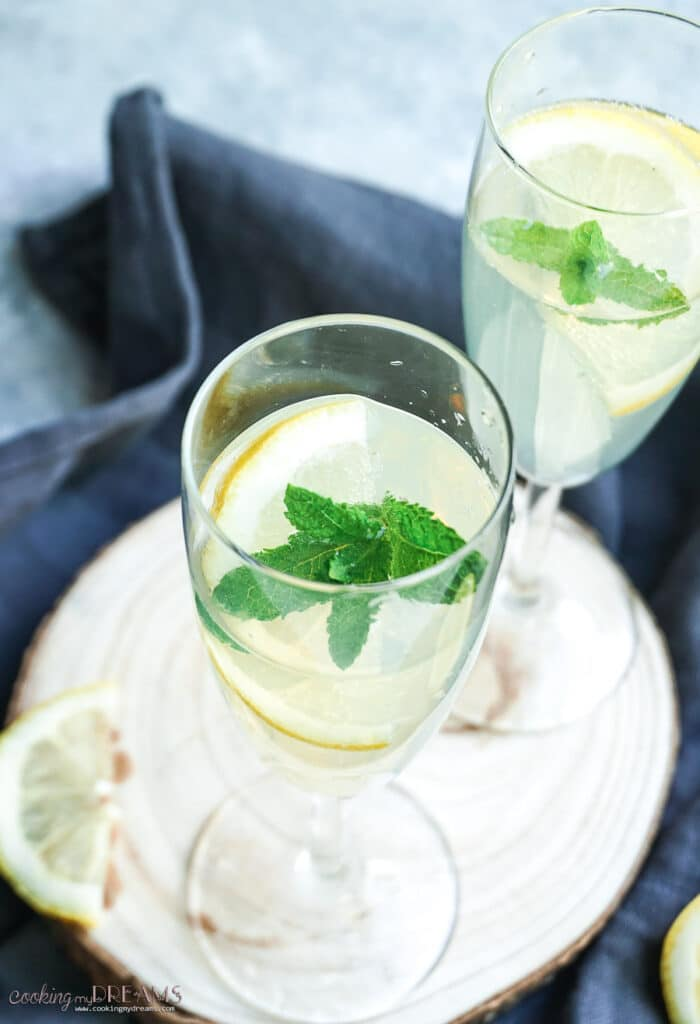 close up of two glasses with limonsecco drink, lemon slices and mint