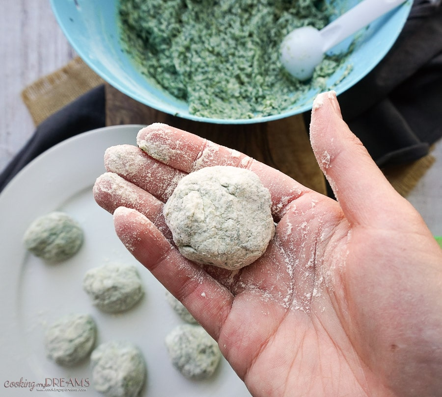 process shot of hand holding a raw ricotta gnocchi