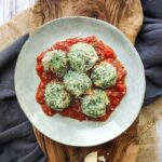 plate on a wooden board with tomato sauce and spinach and ricotta gnocchi