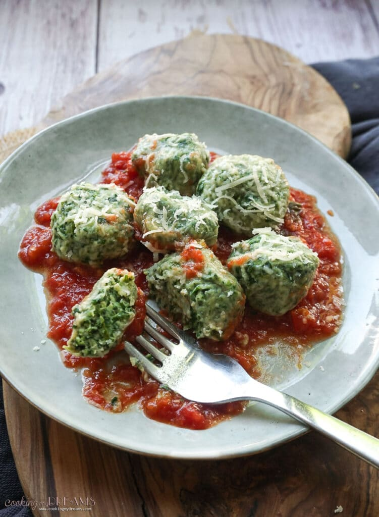 plate on a wooden board with tomato sauce and spinach and ricotta gnocchi with a fork