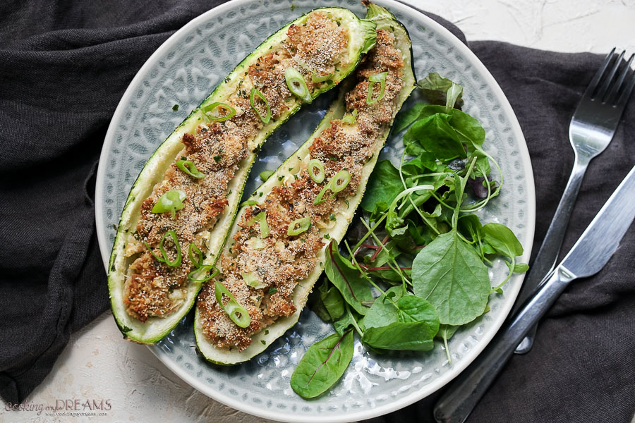 2 stuffed zucchini on a plate with salad