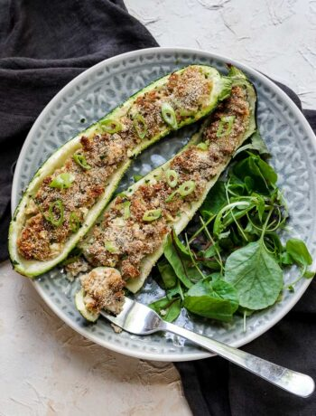 2 stuffed zucchini on a plate with salad with a fork