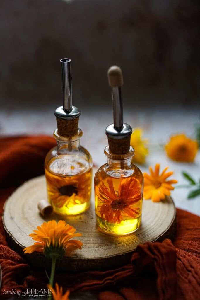 two bottles of marigold oil on a wooden board
