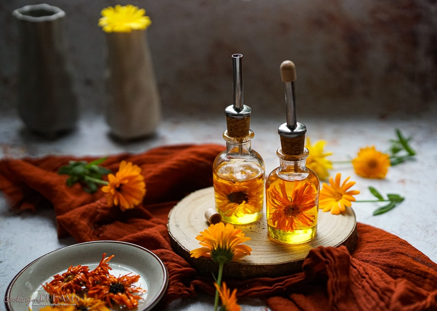 bottles of calendula oil surrounded by marigold flowers