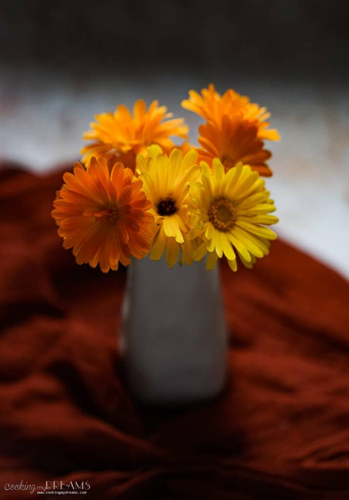calendula flowers in a vase on a red towel